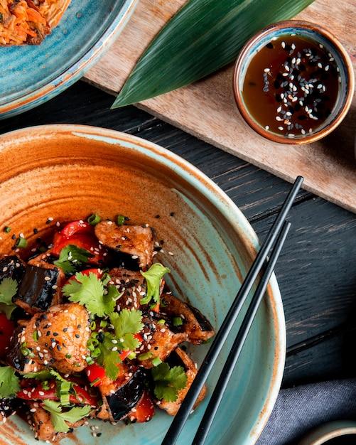 木の上の醤油を添えて揚げナストマトハーブとゴマをボウルに野菜サラダの平面図 無料写真