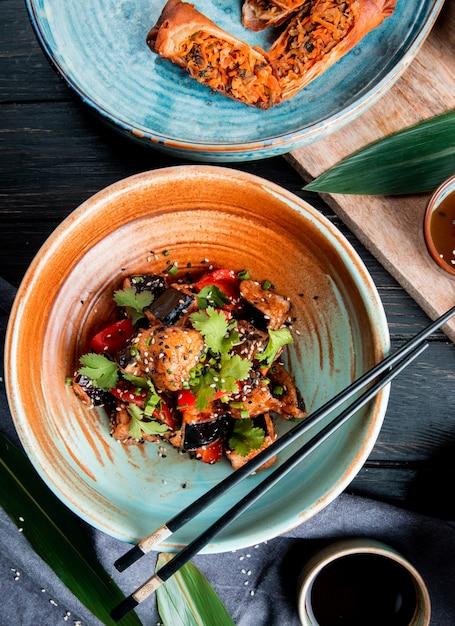 揚げナストマトハーブとゴマのボウルに野菜サラダの上から見ると木の醤油添え 無料写真