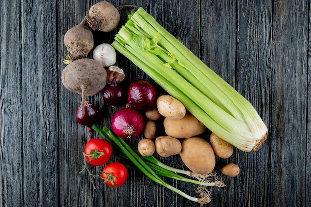 コピースペースを持つ木製の背景にセロリビートの根ニンニクタマネギトマトとネギとして野菜のトップビュー 無料写真