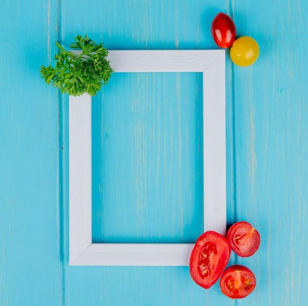 コピースペースを持つ青い表面にコリアンダーと白いフレームとトマトとして野菜のトップビュー 無料写真