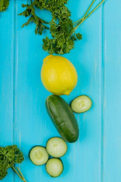 青い表面にレモンとキュウリのコリアンダーとして野菜のトップビュー 無料写真