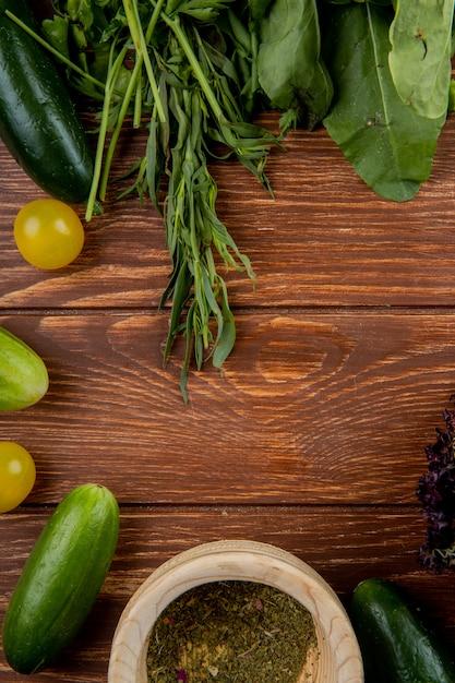 木の表面に黒胡椒でキュウリトマトミントほうれん草として野菜のトップビュー 無料写真