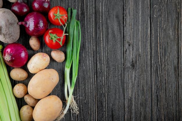 タマネギポテトセロリトマトとネギの左側とコピースペースを持つ木製の背景として野菜のトップビュー 無料写真