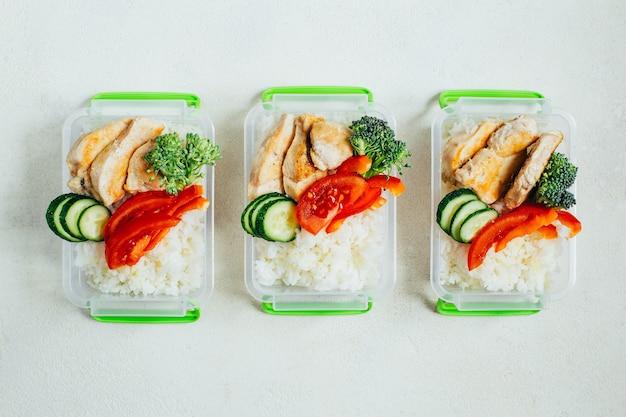 明るい白い表面のプラスチック製のボウルに野菜、米、肉の上面図 Premium写真