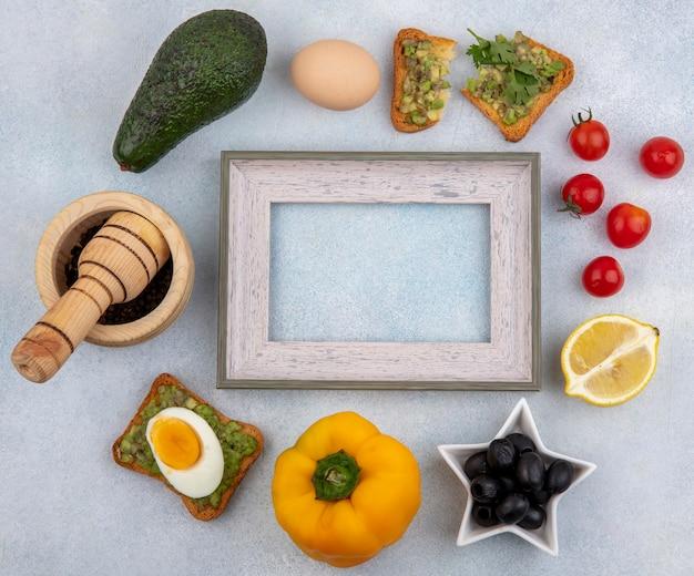 Вид сверху овощей, таких как авокадо, лимон, черные маслины, помидоры, желтый перец и ломтик хлеба с мякотью авокадо на белой поверхности. Бесплатные Фотографии