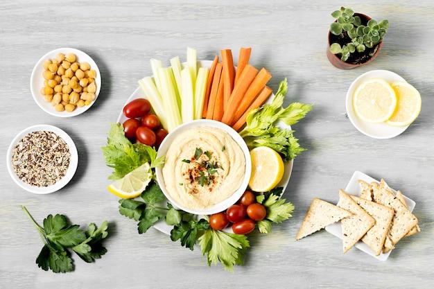 Вид сверху овощей с хумусом и крекерами Premium Фотографии