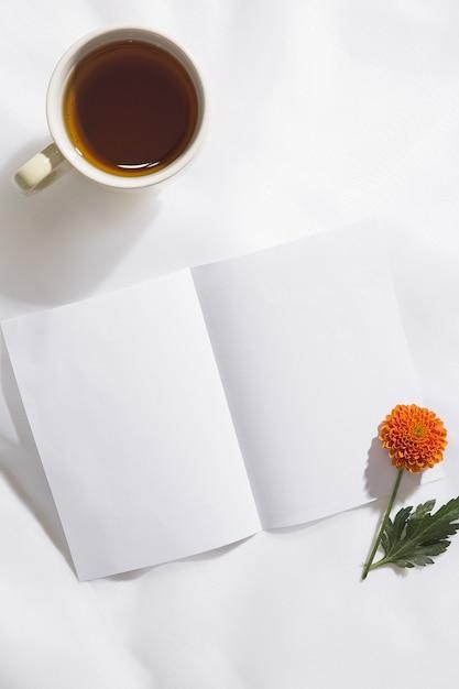 Взгляд сверху предпосылки ткани вуали с кружкой чая, оранжевого цветка и куска белой бумаги с космосом для текста Premium Фотографии