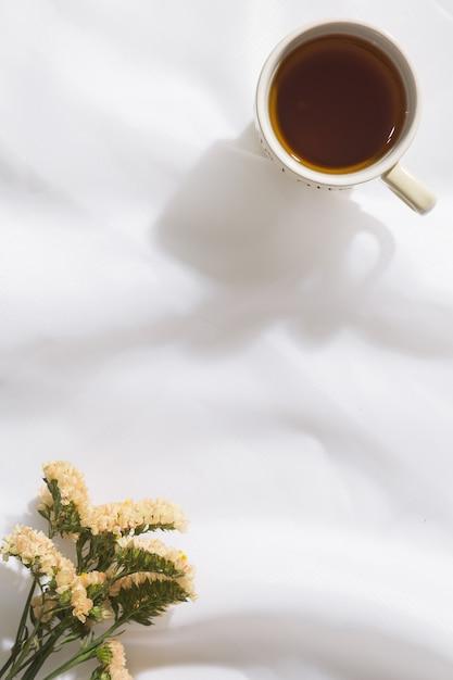 Взгляд сверху предпосылки ткани вуали с кружкой чая и цветков с космосом для текста Premium Фотографии