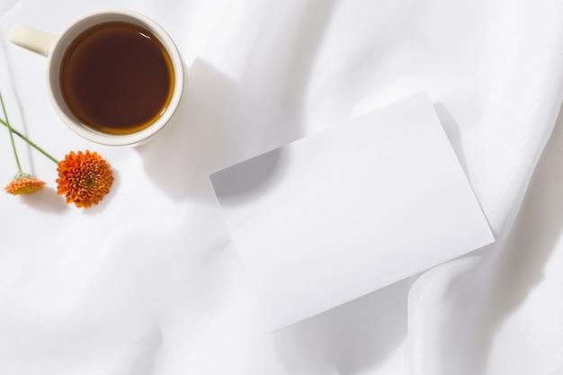 Взгляд сверху предпосылки ткани voile с кружкой чая, 2 оранжевых цветков и куска белой бумаги с космосом для текста. горизонтальный Premium Фотографии