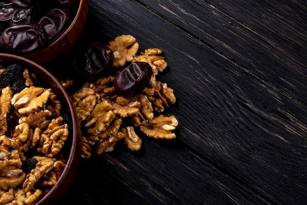 Вид сверху грецких орехов в миску и сладких сушеных фруктов на деревянные Бесплатные Фотографии