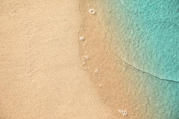 해변에서 모래를 만지고 물의 상위 뷰 프리미엄 사진