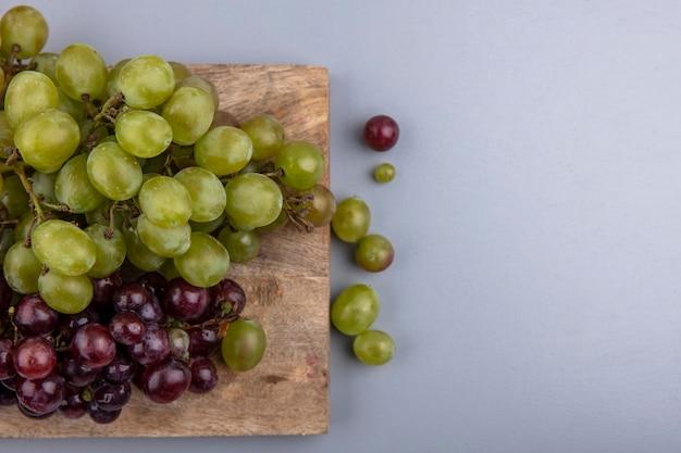 まな板とコピースペースと灰色の背景に白と赤のブドウのトップビュー 無料写真