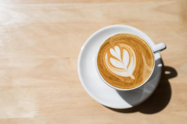 朝の日差しと影の下で木製のテーブルにミルクフォームハート形のアートとホットコーヒーカフェラテの白いカップの平面図です。 Premium写真