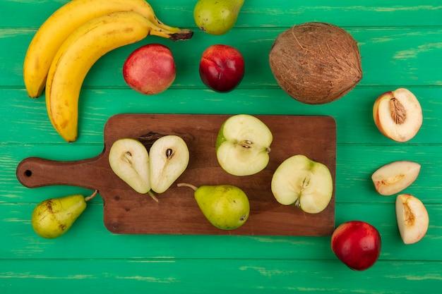 緑の背景に桃バナナココナッツとまな板の上の梨リンゴとして全体と半分カットフルーツのトップビュー 無料写真