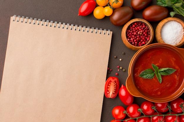 Вид сверху на зимний томатный суп в миске с блокнотом Premium Фотографии