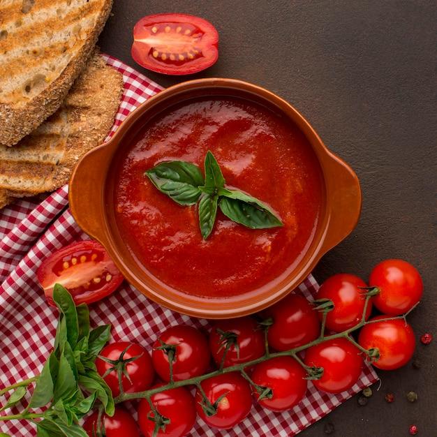 トーストとテーブルクロスのボウルに冬のトマトスープの上面図 無料写真