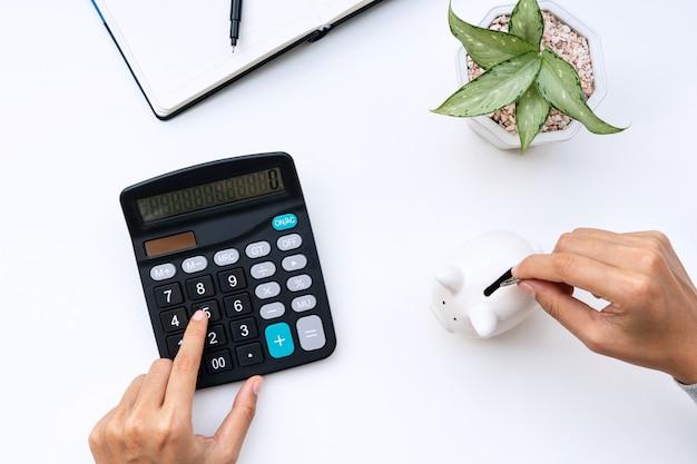 Вид сверху руки женщины кладя монету в копилку при использовании калькулятора на белом столе дома. Premium Фотографии