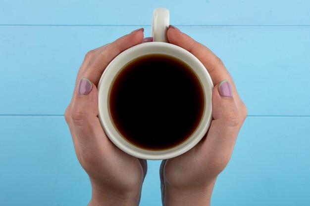 青の背景にお茶のカップを保持している女性の手の上から見る 無料写真