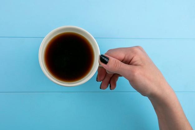 Взгляд сверху рук женщины держа чашку чая на голубой предпосылке Бесплатные Фотографии