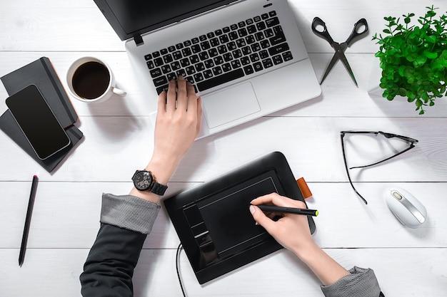 ノートパソコンのキーパッドで入力する女性の手の平面図は、コーヒーカップと白いオフィスのデスクトップに配置されます。 Premium写真