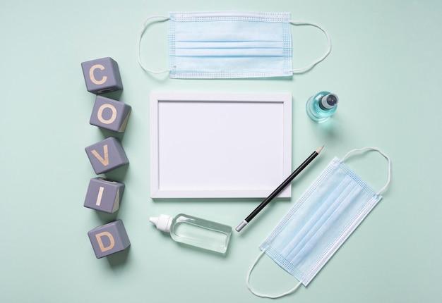Вид сверху деревянных кубиков с ковидом и рамкой рядом с медицинскими масками Premium Фотографии