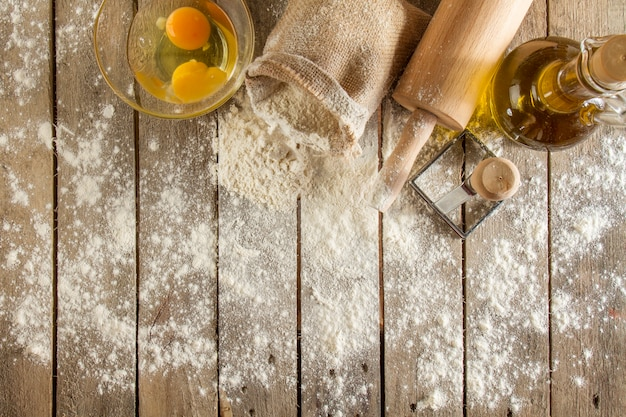 Top view of wooden surface with flour, eggs and rolling pin Free Photo