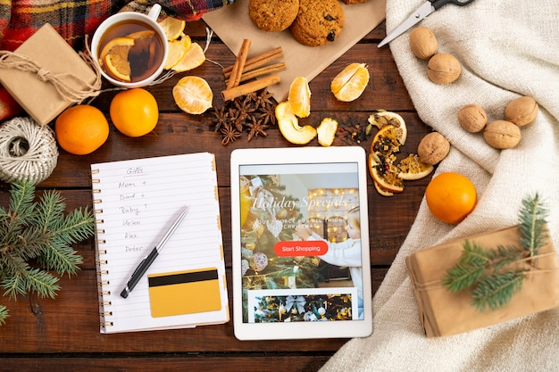 Вид сверху рождественского промо в планшете, пластиковой карточке, ручке в рождественском списке в окружении других праздничных вещей на столе Premium Фотографии