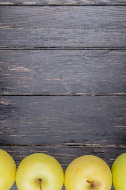 コピースペースを持つ木製の背景に黄色のリンゴのトップビュー 無料写真