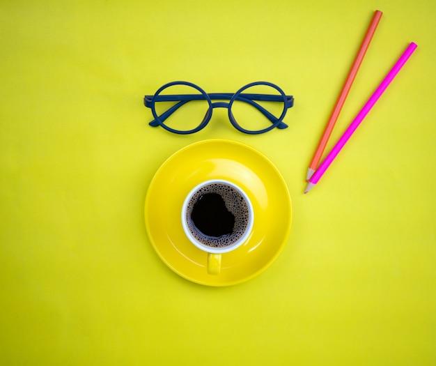 黄色の紙の背景に先生のメガネとカラフルな鉛筆と黄色のコーヒーカップの上面図 Premium写真