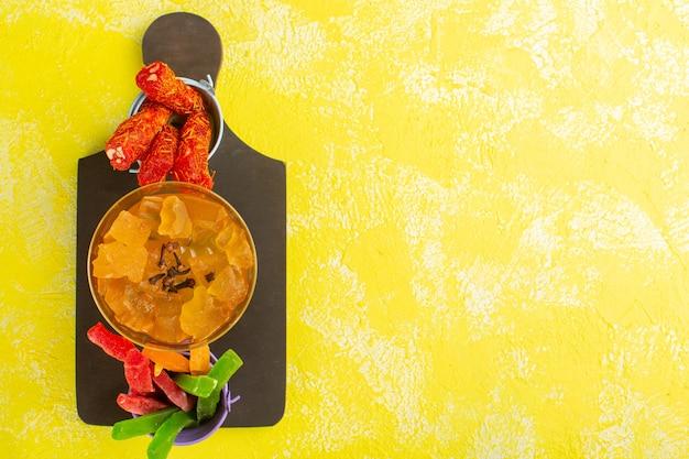 Вид сверху желтых желе с нугой и мармеладом на желтой поверхности Бесплатные Фотографии