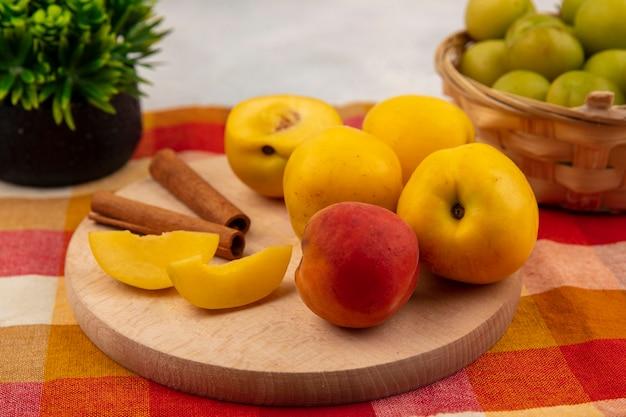 Вид сверху желтых персиков на деревянной кухонной доске с палочками корицы с зелеными алычами на ведре на клетчатом фоне скатерти Бесплатные Фотографии