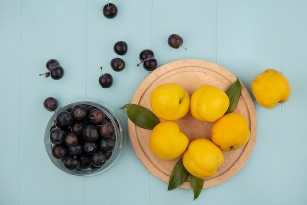 Вид сверху желтых персиков на деревянной кухонной доске с темно-фиолетовыми кислыми тернами на стеклянной миске на синем фоне Бесплатные Фотографии