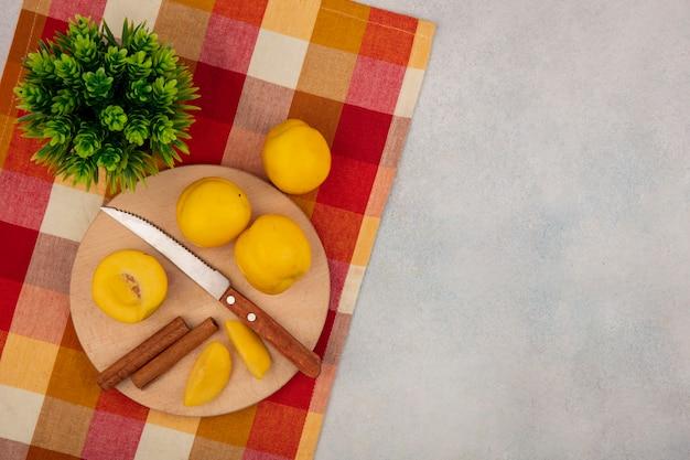 Вид сверху желтых персиков на деревянной кухонной доске с ножом с палочками корицы на проверенной скатерти на белом фоне с копией пространства Бесплатные Фотографии
