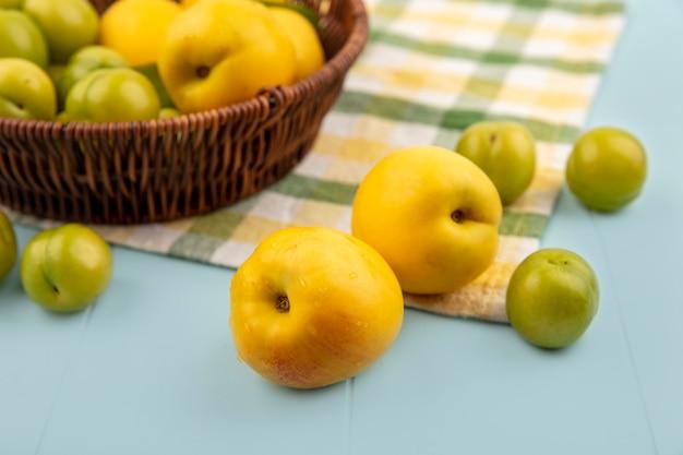 Вид сверху желтых персиков с зелеными алычами на клетчатой скатерти на синем фоне Бесплатные Фотографии