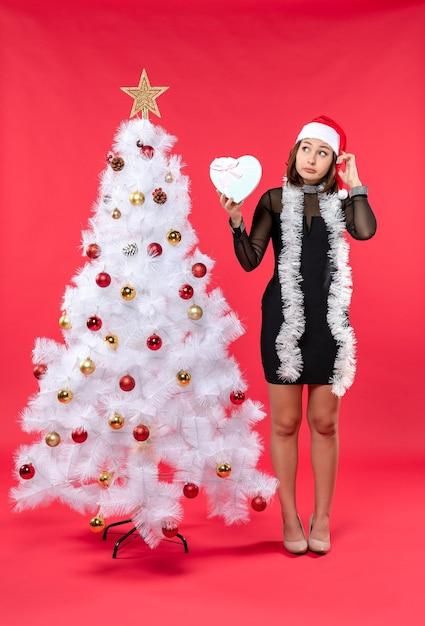 Вид сверху молодой девушки в черном платье в шляпе санта-клауса, стоящей возле рождественской елки и держащей сердце на красном Бесплатные Фотографии