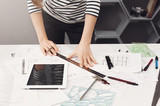 캐주얼 스트라이프 셔츠와 검은 청바지 테이블 근처에 서, 손으로 통치자와 펜을 들고 그림을 만들고, 디지털 테이블에서 영화를보고, 젊은 잘 생긴 건축가 학생 소녀의 상위 뷰 Gett 무료 사진