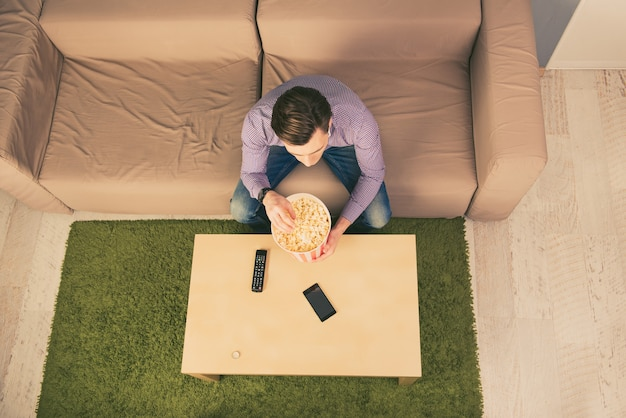 Вид сверху на молодого человека, отдыхающего дома, смотрящего фильм и едящего попкорн Premium Фотографии