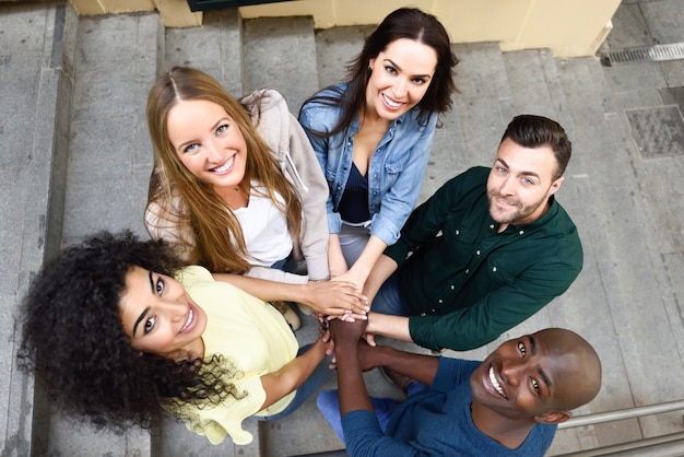 Top view of young people putting their hands together. Free Photo
