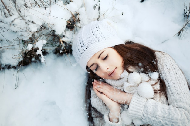 Top view of young woman sleeping on the snowy ground Free Photo