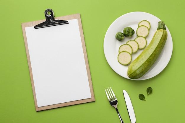 브뤼셀 새싹 및 클립 보드와 함께 접시에 호박의 상위 뷰 프리미엄 사진