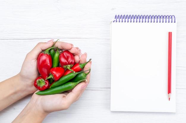軽くて野菜の辛い辛い食べ物の食事にメモ帳を付けた女性がスパイシーにホールドした唐辛子の上面図 無料写真