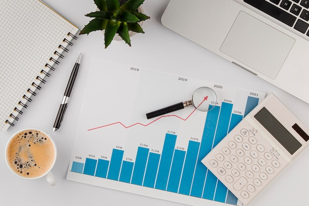 Top view of office desk with growth chart and calculator Free Photo
