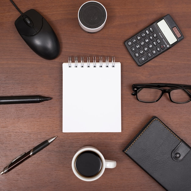 Top view of office stationery; coffee cup; with bluetooth speaker; eyeglass on wooden desk Free Photo