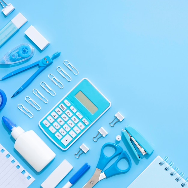 Top view of office stationery with calculator and stapler Free Photo