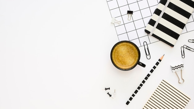 Top view of office stationery with coffee and paper clips Free Photo