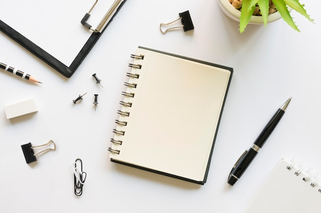 Top view of office stationery with notebook and pins Free Photo