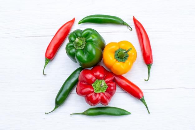白、野菜のスパイスの温かい食べ物の食事の材料製品にスパイシーな唐辛子を添えたフルベルペッパーの上面図 無料写真