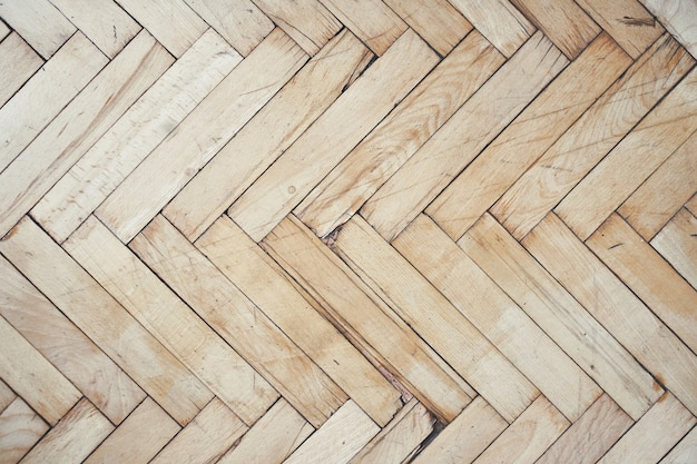 Top view of old brushed and distressed wooden parquet floor made from many racks in herringbone pattern Free Photo