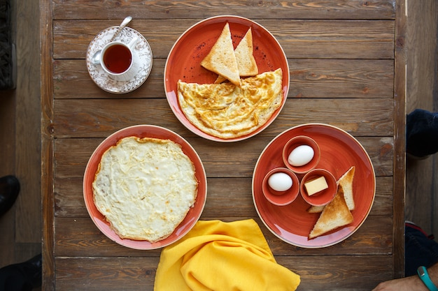 Top view of omelette plates and boiled eggs, toast and butter Free Photo
