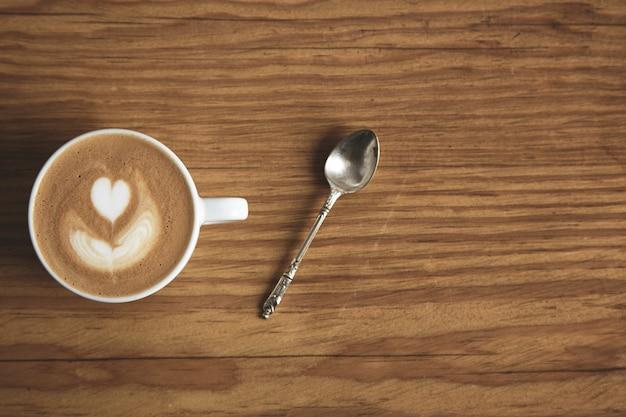 カフェショップの厚い残忍な木製のテーブルに銀のスプーンでカプチーノと空白の白いカップの上面図。ハート型の泡。トップカップに焦点を当てる 無料写真